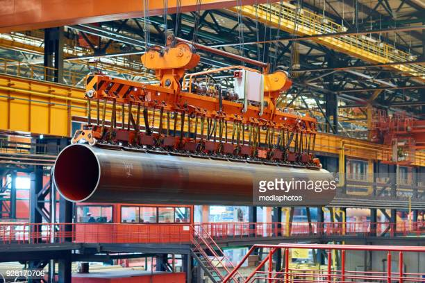 bridge crane moving with large tube - crane construction machinery stock pictures, royalty-free photos & images