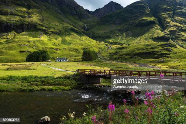 Bridge crossing the river Coe to cottage at Glencoe Highlands , Scotland