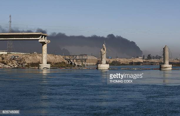 Bridge destroyed by Islamic State group jihadists is seen in front of black plumes of smoke from burning oil wells, set ablaze by retreating IS...