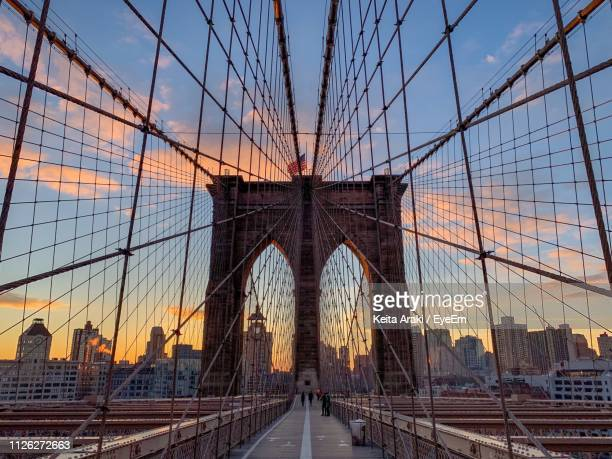 bridge in city against sky during sunset - lower manhattan stock pictures, royalty-free photos & images
