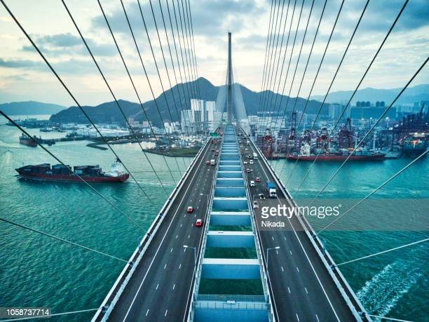 bridge in hong kong and container cargo freight ship - suspension bridge stock photos and pictures