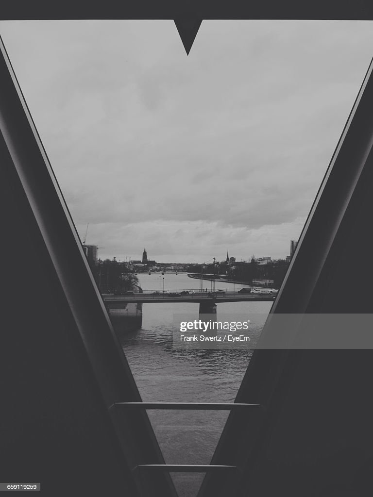Bridge In River Seen Through Window Against Cloudy Sky : Stock-Foto