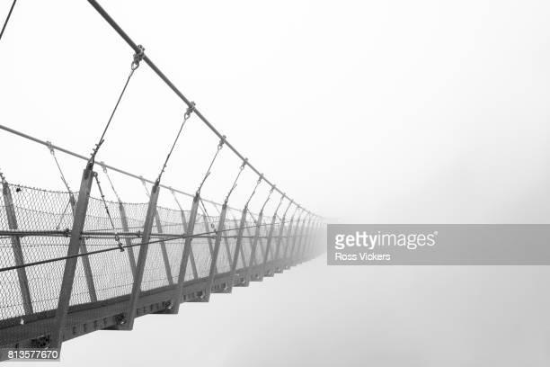 bridge into the mist - hängebrücke stock-fotos und bilder