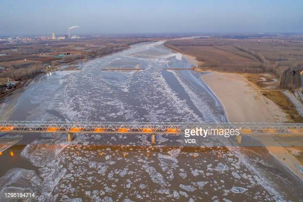 Bridge is illuminated as ice floes appear on the Yellow River on January 7, 2021 in Binzhou, Shandong Province of China.