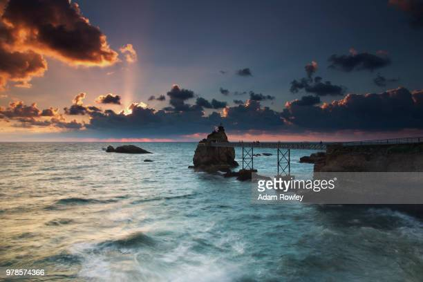 bridge leading to small rocky island on sea at sunset, biarritz, northern basque country, pyrenees-atlantiques, france - biarritz stock pictures, royalty-free photos & images