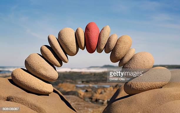 bridge made from stones, red one in centre - pebble stock pictures, royalty-free photos & images