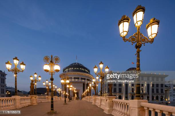 bridge of art and state buildings at dusk - skopje stock pictures, royalty-free photos & images