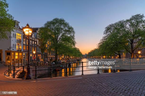 bridge on a canal in amsterdam at dusk - amsterdam stock pictures, royalty-free photos & images