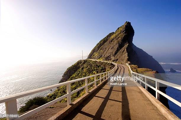 Bridge on a mountain with blue ocean all around