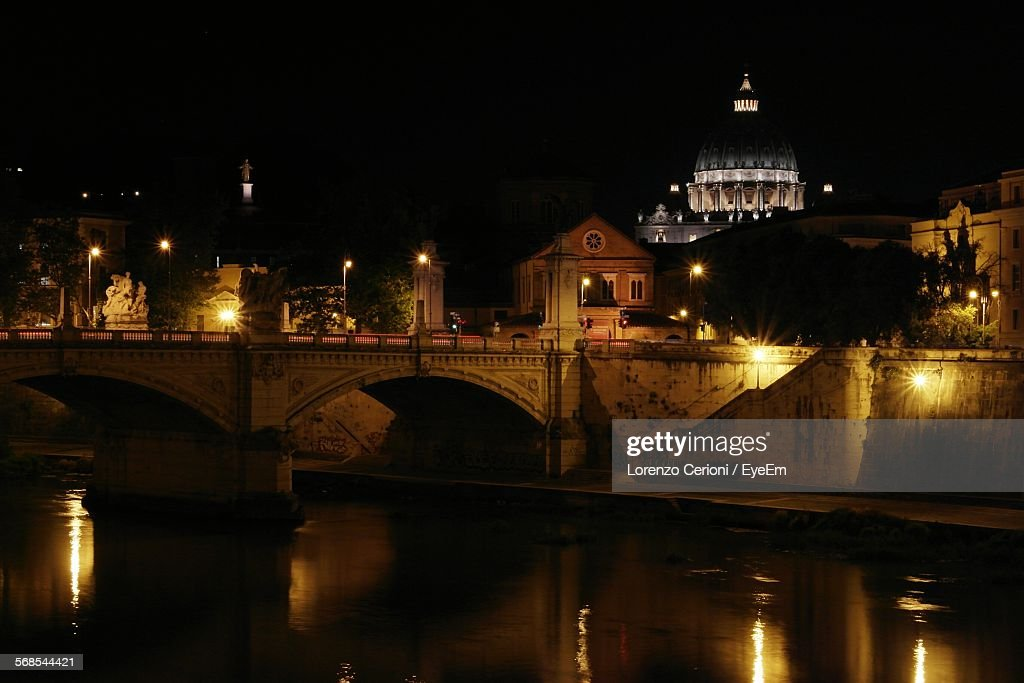 Bridge On River By Buildings In City At Night : Stock Photo