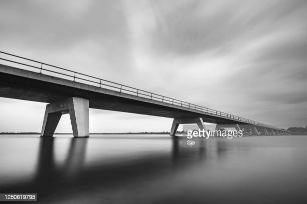 "bridge over a lake with smooth water and sky in black and white - ""sjoerd van der wal"" or ""sjo"" stock pictures, royalty-free photos & images"