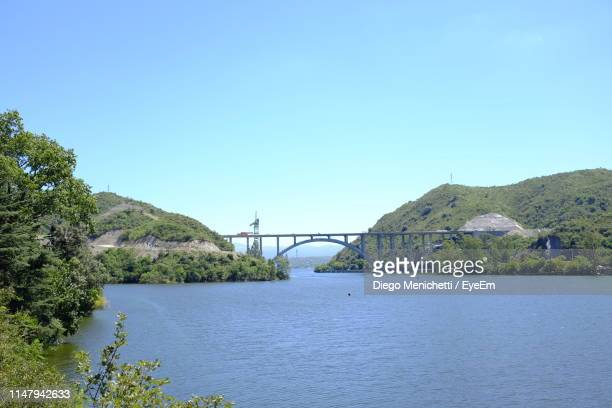 bridge over calm river against clear sky - cordoba argentina stock photos and pictures