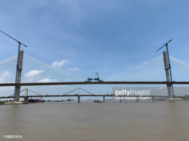 bridge over calm river against sky - barranquilla stock pictures, royalty-free photos & images