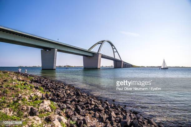 bridge over calm sea against clear sky - fehmarn stock-fotos und bilder