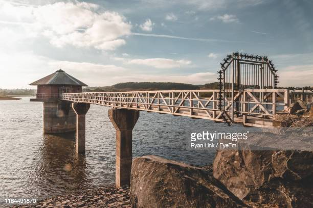 bridge over calm sea against cloudy sky - leicester stock pictures, royalty-free photos & images