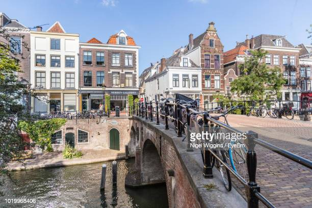 bridge over canal amidst buildings in city against sky - utrecht stockfoto's en -beelden