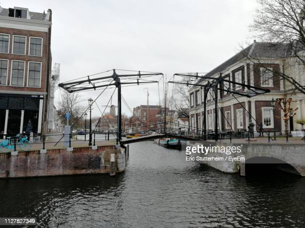 bridge over canal amidst buildings in city against sky - stutterheim stock photos and pictures