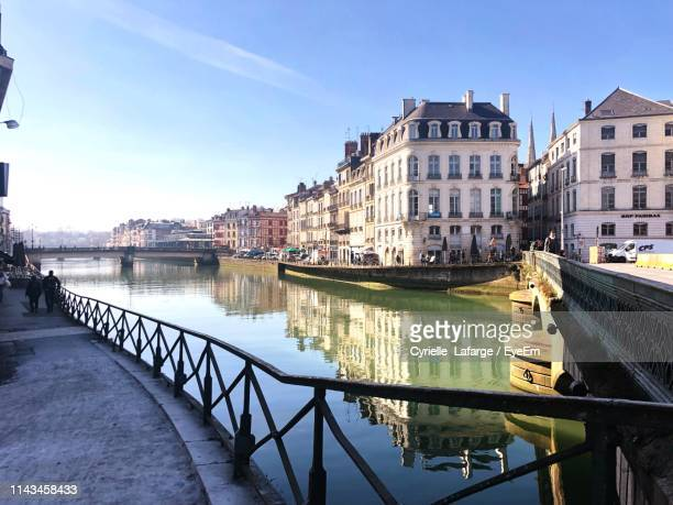 bridge over canal amidst buildings in city against sky - ピレネーアトランティーク ストックフォトと画像