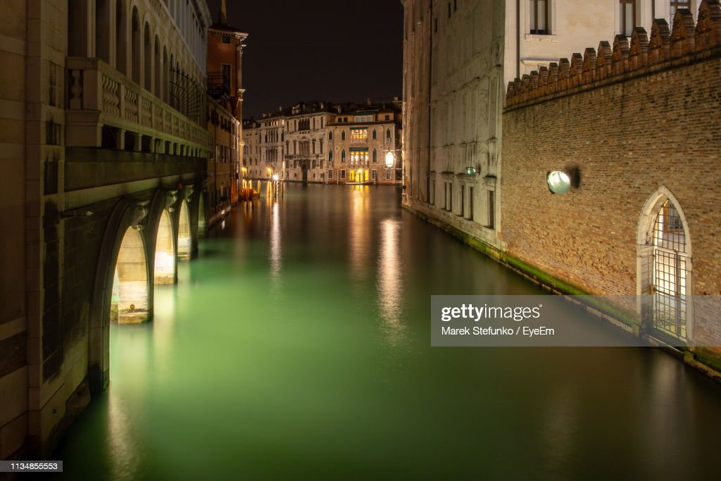 Bridge Over Canal Amidst Buildings In City At Night : Stock Photo