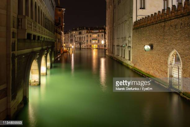 bridge over canal amidst buildings in city at night - marek stefunko stock photos and pictures