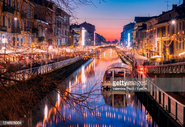 bridge over canal amidst buildings in city - milan stock pictures, royalty-free photos & images
