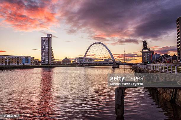bridge over clyde river against cloudy sky in city during sunset - glasgow stock pictures, royalty-free photos & images