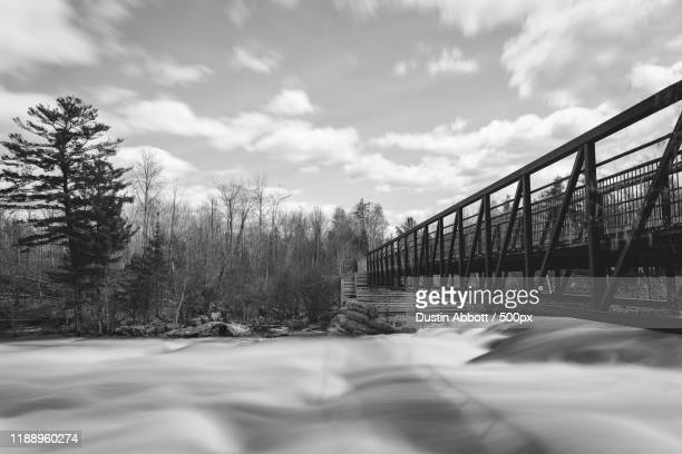 bridge over flowing river - dustin abbott - fotografias e filmes do acervo