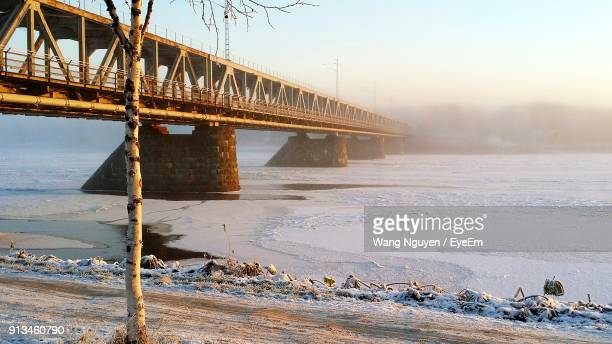 Bridge Over Frozen Lake Against Clear Sky During Winter