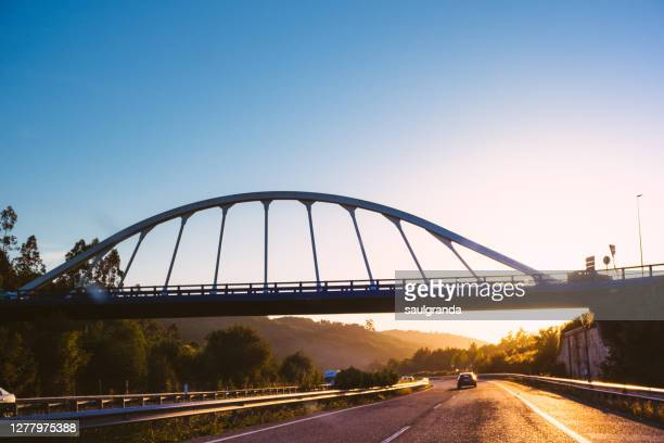 bridge over highway at sunset - asturias stock pictures, royalty-free photos & images