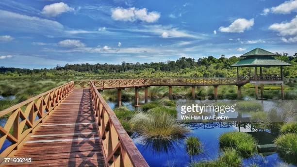 bridge over lake against sky - brunei stock pictures, royalty-free photos & images