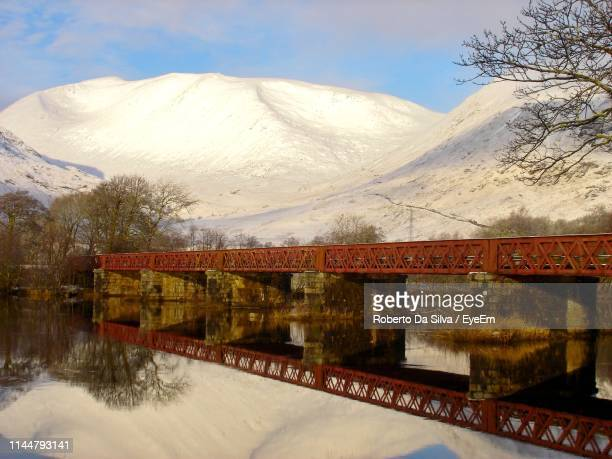 bridge over lake by snowcapped mountains against sky - strathclyde stock pictures, royalty-free photos & images