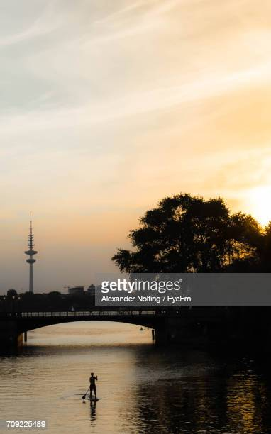 bridge over lake with heinrich-hertz-turm in background against sky during sunset - hertz stock pictures, royalty-free photos & images