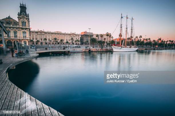 bridge over river against buildings in city - barcelona spanien stock-fotos und bilder