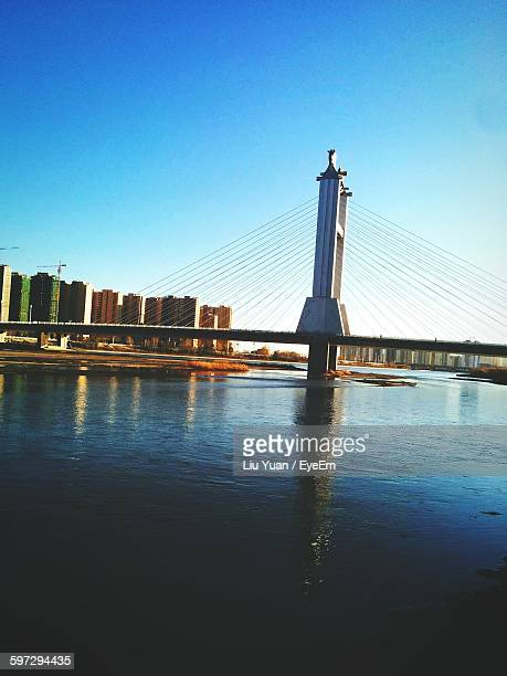 bridge over river against clear blue sky - liu he stock pictures, royalty-free photos & images