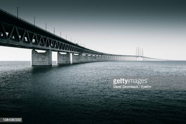 bridge over river against clear sky - regione dell'oresund foto e immagini stock