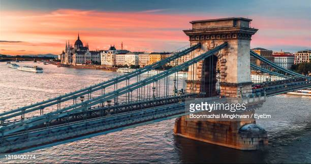 bridge over river against cloudy sky and sunset - hungary stock pictures, royalty-free photos & images