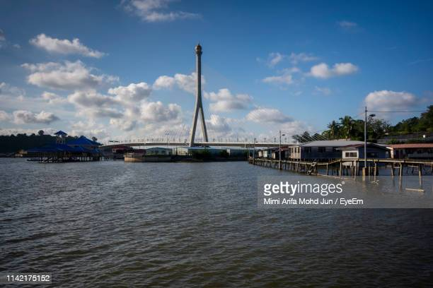 bridge over river against cloudy sky - bandar seri begawan stock photos and pictures