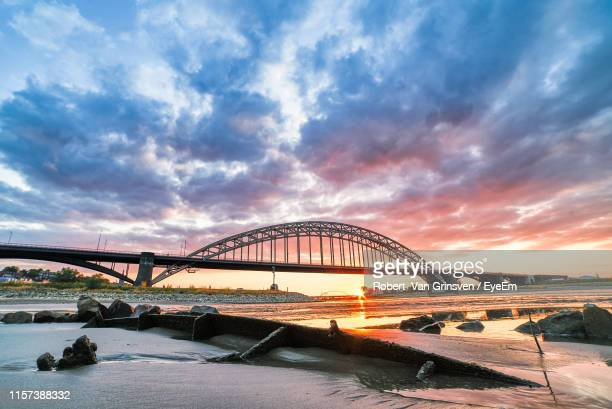 bridge over river against cloudy sky - nijmegen stock pictures, royalty-free photos & images