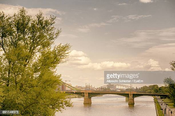 bridge over river against cloudy sky - albrecht schlotter stock photos and pictures