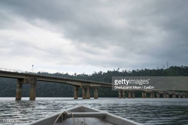 bridge over river against cloudy sky - shaifulzamri stock pictures, royalty-free photos & images