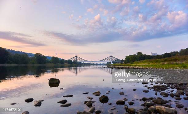 bridge over river against sky at sunset - rademann stock pictures, royalty-free photos & images
