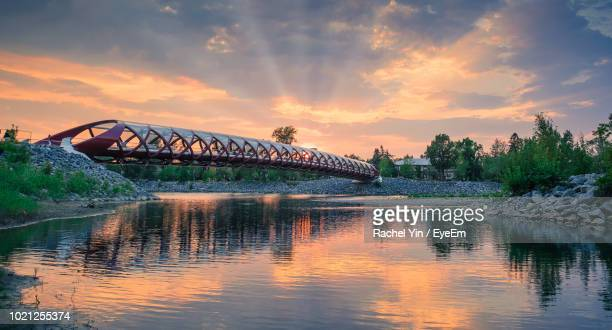 bridge over river against sky during sunset - calgary stock pictures, royalty-free photos & images
