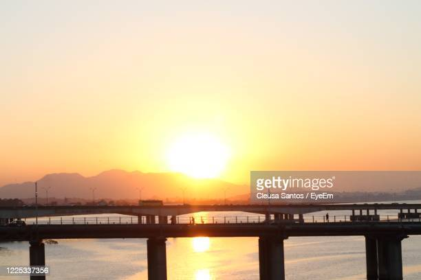 bridge over river against sky during sunset - pôr do sol stock pictures, royalty-free photos & images