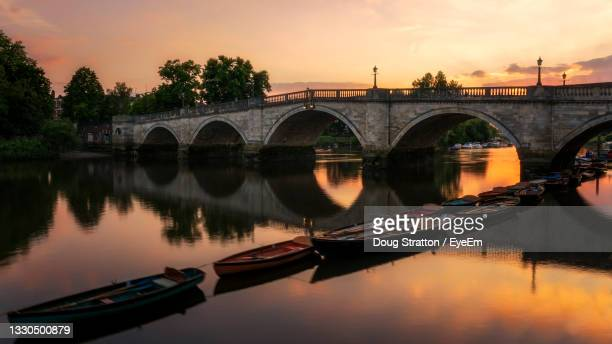bridge over river against sky during sunset - canal stock pictures, royalty-free photos & images