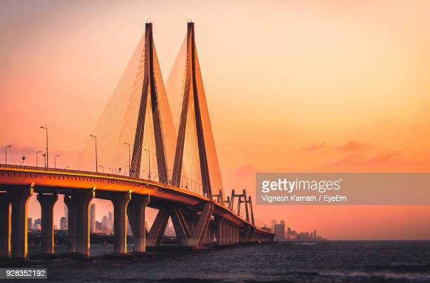 bridge over river against sky during sunset - ムンバイ ストックフォトと画像