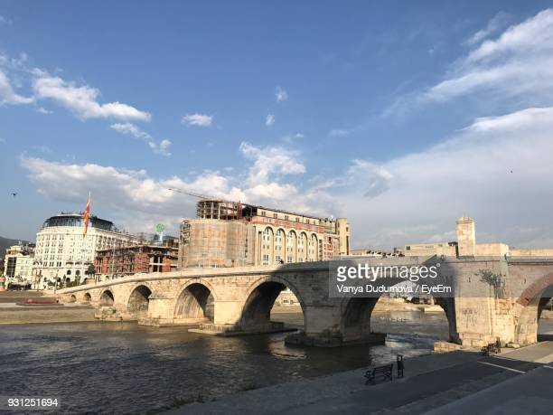 bridge over river against sky in city during sunset - skopje stock pictures, royalty-free photos & images