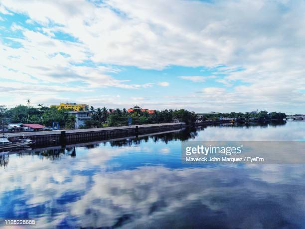 bridge over river against sky in city - malabon stock pictures, royalty-free photos & images