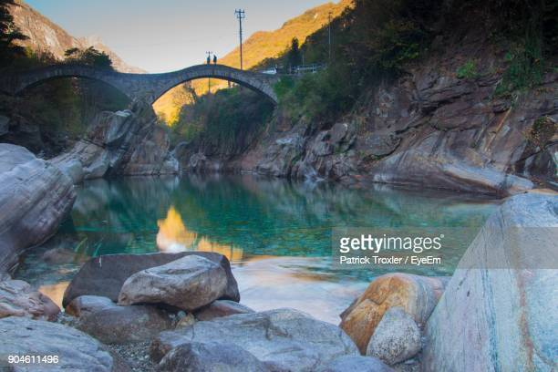 bridge over river against sky - locarno stock photos and pictures