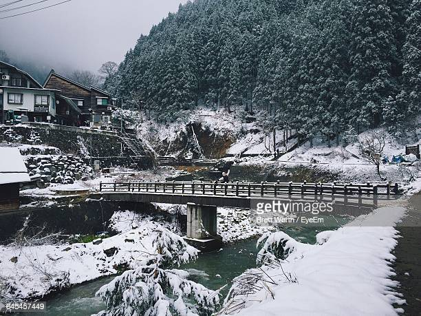 Bridge Over River Against Trees During Winter