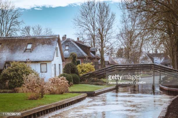 bridge over river amidst bare trees and buildings against sky - giethoorn stock pictures, royalty-free photos & images